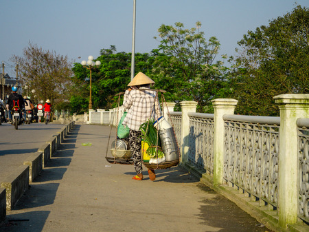 Hue, Vietnam - September 13 2017: Unidentified woman crossing the bridge and carrying in her shoulders the food in the city of Hue, Vietnam
