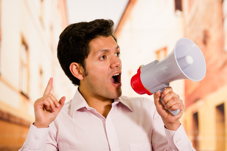Close up of a handsome man screaming with a megaphone, doing a signal with his hand in a blurred background Stock Photo
