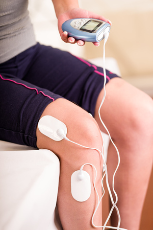 Close-up of a deportist holding with one hand the electric machine and the electrostimulator electrodes in her leg