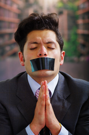 criminal: Businessman with a black tape in his mouth asking for mercy , in a blurred background