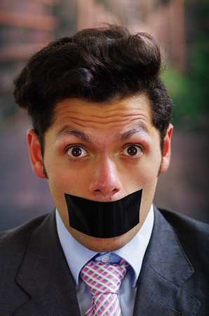 criminal: Portrait of a desperate businessman, with a black tape in his mouth, in a blurred background