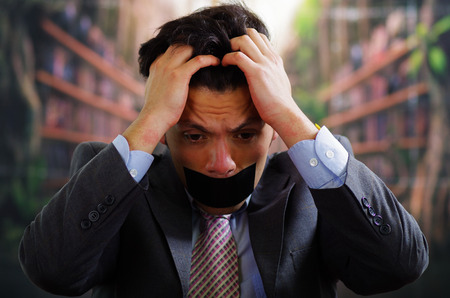 criminal: Businessman with a black tape in his mouth, and touching his hair with desperation, in a blurred background
