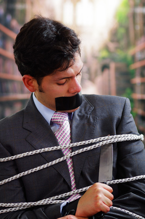 Businessman trapped in a chair with rope, with a black tape in his mouth, trying to cut the rope with a knife, in a blurred background Stock Photo