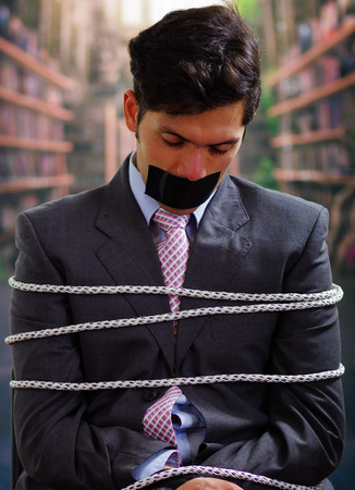 criminal: Businessman trapped in a chair with rope, with a black tape in his mouth in a blurred background Stock Photo