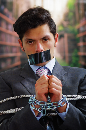 criminal: Close up of a businessman trapped in a chair with rope, with a black tape in his mouth and a chain in his hands, in a blurred background