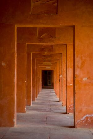 Beautiful view of a stoned path with columns in a row inside of a building at outdoors in the Indian city of Agra, India.