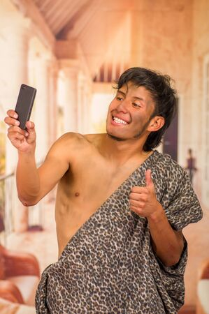 Close up of funny prehistoric man doing funny faces to the camera, taking a selfie with his cellphone and thumbs up, in a blurred background