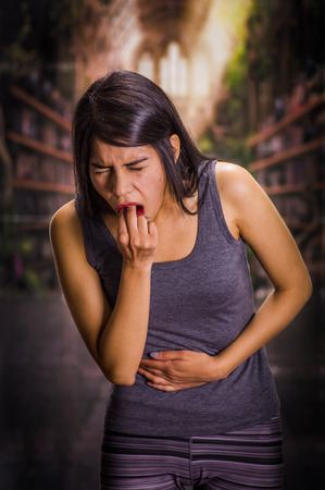 induce: Beautiful and lonely girl suffering of anorexy, holding her stomach and putting his fingers in her mouth to induce to vomit, a blurred background