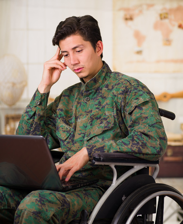 Close up of a thoughtful young soldier sitting on wheel chair using his computer over his legs, wearing military uniform in a blurred background