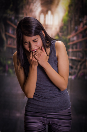 induce: Beautiful and lonely girl suffering of anorexy, putting his fingers in her mouth to induce to vomit, in a blurred background