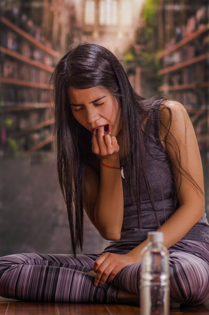 Beautiful and lonely girl suffering of anorexy, putting his fingers in her mouth to induce to vomit, with a bottle of water in front in a blurred background