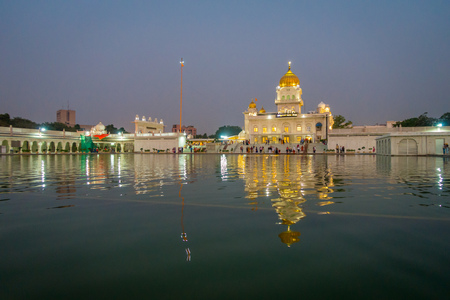 DELHI, INDIA - SEPTEMBER 19, 2017: Unidentified people walking in front of the main Sikh shrines of Delhi - Gurudwara Bangla Sahib. The main building of the temple is illuminated and is reflected in Sarowar pond water in India. Editorial