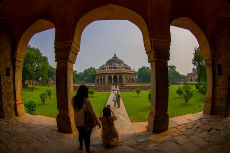 DELHI, INDIA - SEPTEMBER 19, 2017: Unidentified people walking around of the pillars of the Isa Khan Tomb at Humayuns Tomb complex in Delhi, India. Humayuns Tomb was the first garden-tomb on the Indian subcontinent, fish eye effect Editorial