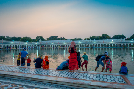 DELHI, INDIA - SEPTEMBER 19, 2017: Unidentified people swimming and washing their heads as lucky in the pond in the Famous Sikh gurdwara Golden Temple Harmandir Sahib in India Editorial