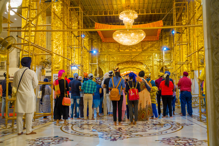 DELHI, INDIA - SEPTEMBER 19, 2017: Beautiful golden walls inside of the temple with crowd of people inside of the Sikh gurdwara Golden Temple Harmandir Sahib, in India