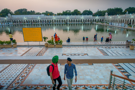 DELHI, INDIA - SEPTEMBER 19, 2017: Unidentified people walking upstairs and dowstairs, while other are swimming and washing their heads as lucky in the pond in the Famous Sikh gurdwara Golden Temple Harmandir Sahib in India