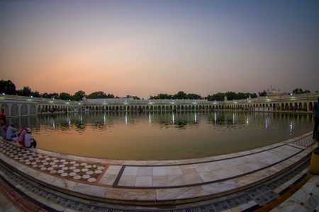 DELHI, INDIA - SEPTEMBER 19, 2017: Beautiful sunset in Famous Sikh gurdwara Golden Temple Harmandir Sahib reflected in the artificial pond in India Editorial