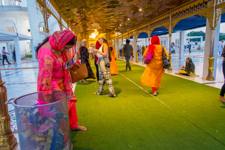 DELHI, INDIA - SEPTEMBER 19, 2017: Unidentified people walking in the plaza over a green carpet, with a woman deposit plastic botle in a metallic trasin the Famous Sikh gurdwara Golden Temple Harmandir Sahib in India Editorial