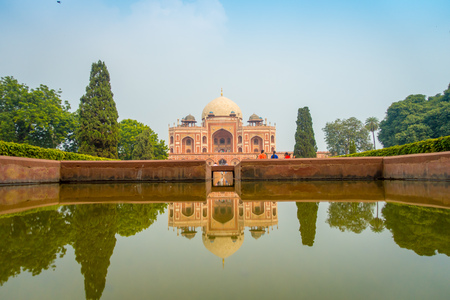 DELHI, INDIA - SEPTEMBER 19, 2017: Beautiful artificial fountain with a Mogul King Humayuns Tomb reflected in the water, in New Delhi India. Editorial