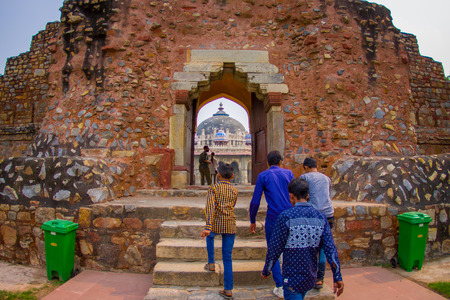 DELHI, INDIA - SEPTEMBER 19, 2017: Unidentified people crossing a stoned enter to the Isa Khan Tomb at Humayuns Tomb complex in Delhi, India. Humayuns Tomb was the first garden-tomb on the Indian subcontinent, fish eye effect