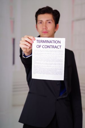 Close up of boss wearing a suit and giving a sheet of paper of termination of contract text on it, in a blurred background Stock Photo