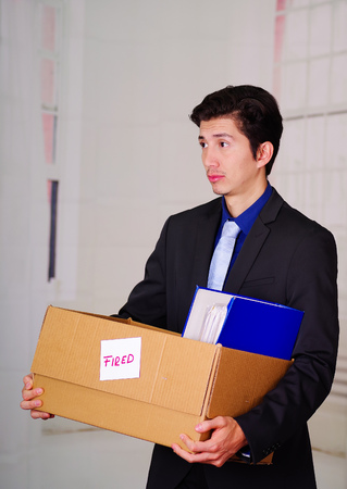 Close up of sad man holding a box after being fired from his job in a blurred background