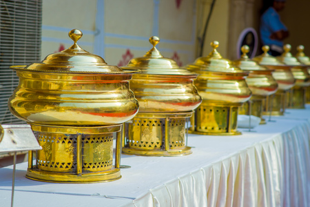 Close up of golden structures put in a raw over a table with white fabric, in City Palace in Jaipur, India Stock Photo