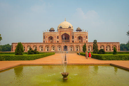 DELHI, INDIA - SEPTEMBER 19, 2017: Unidentified people walking in front of a Mogul King Humayuns Tomb in New Delhi, India with an artificial fountain in front Editorial