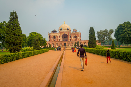 DELHI, INDIA - SEPTEMBER 19, 2017: Unidentified people walking in front of a Mogul King Humayuns Tomb in a stoned ground during a sunny day in New Delhi, India