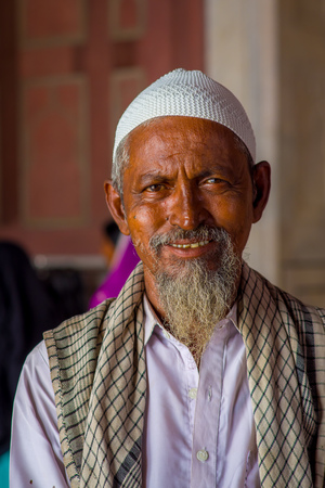 Delhi, India - September 27, 2017: Portrait of a man with white beard looking at camera inside of the temple in Jama Masjid Mosque in Delhi, India in a blurred background