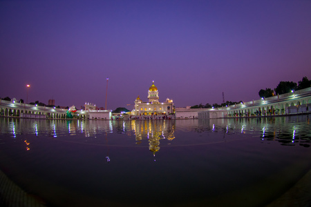 DELHI, INDIA - SEPTEMBER 19, 2017: Beautiful view of the Famous Sikh gurdwara Golden Temple Harmandir Sahib reflected in the artificial pond, with a gorgeous purple sky in India