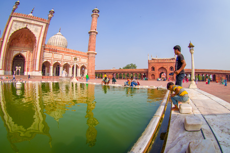 DELHI, INDIA - SEPTEMBER 27, 2017: Clos eup of unidentified people walking near of the artificial pond in front of a beautiful Jama Masjid temple, this is the largest muslim mosque in India. Delhi, India, fish eye effect Editorial