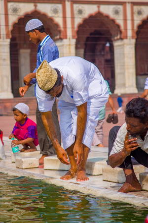 Delhi, India - September 27, 2017: Close up of Unidentified man washing his arms using the water of the pong in the courtyard of Jama Masjid Mosque in Delhi, India Editorial