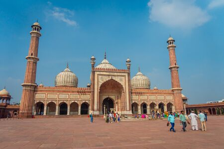 Delhi, India - September 27, 2017: Unidentified indian tourists visiting Jama Masjid, in Delhi, India. Jama Masjid is the largest and perhaps the most magnificent mosque in India in a beautiful day with blue sky