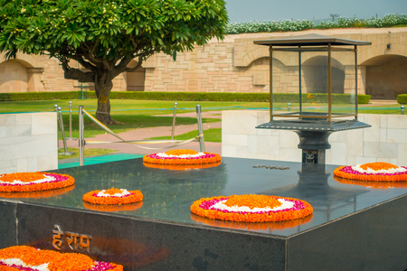 DELHI, INDIA - SEPTEMBER 25 2017: Modern grave in Rajghat, New Delhi as memorial at Mahatma Gandhis body cremation place, with some beautiful flowers over the grave in Delhi India