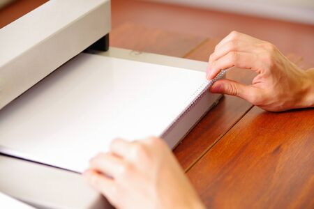 Man organizing the documents using his hands to binding documents using a plastic ring binder machine, over a wooden table