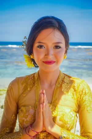 BALI, INDONESIA - MARCH 11, 2017: Beautiful woman in thai traditional dress in the beach of Pantai pandawa, in Bali island, Indonesia.