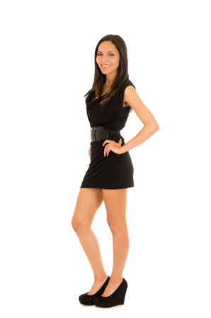 Beautiful smiling young woman, wearing a black dress and posing for camera, in a white background