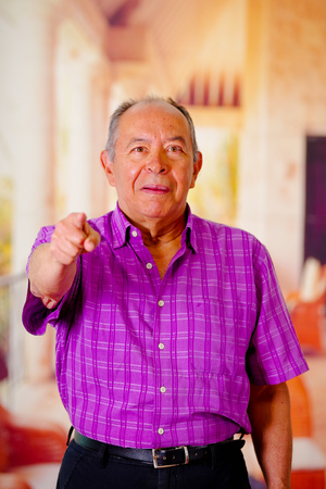 Close up of a happy old man, pointing with his hand in front and wearing a purple square t-shirt in a blurred background Stock Photo