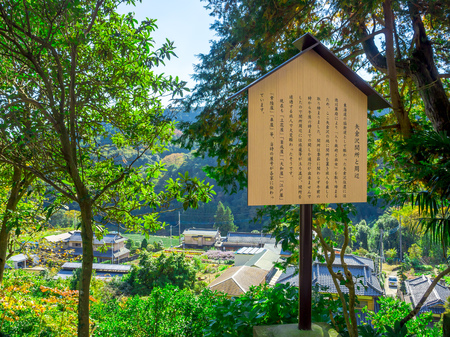 TOKYO, JAPAN JUNE 28 - 2017: Informative sign of japanesse letter with a beautiful landscape of the mountain with some houses, in a gorgeous blue sky
