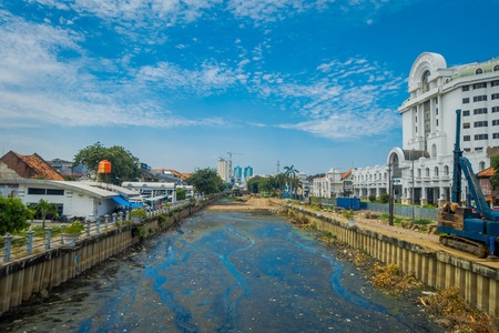 JAKARTA, INDONESIA - MAY 06, 2017: Charming water channel passing through Jakarta seen from bridge, residence buildings alongside. beautiful blue sky Editorial