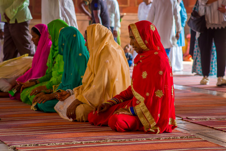 Delhi, India - September 27, 2017: Close up of unidentified group of women wearing colorful hijab sitting in the floor and praying at the Jama Masjid Mosque inside of the temple in Delhi