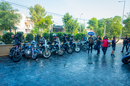 DELHI, INDIA - SEPTEMBER 19, 2017: Unidentified group men, members of Harley Davidson moto club, next to their motorcycles in the sreets of Delhi Royal Enfield Motorcycle, travelling in Delhi