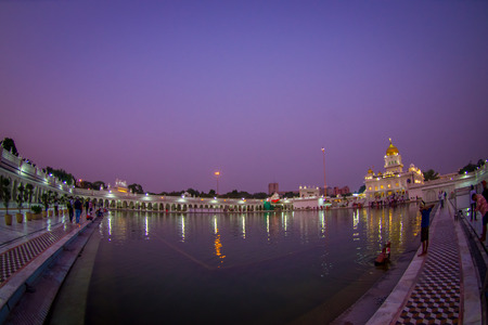 DELHI, INDIA - SEPTEMBER 19, 2017: Unidentified people swiming and walking near of the artificail pond, with a beautiful view of the Famous Sikh gurdwara Golden Temple Harmandir Sahib reflected in the artificial pond, with a gorgeous purple sky in India Editorial