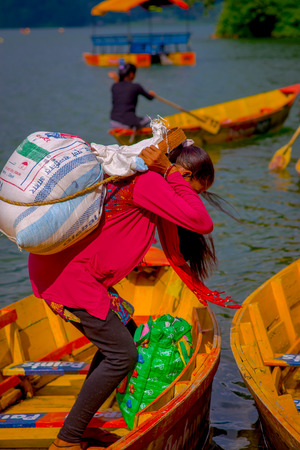 phewa: POKHARA, NEPAL - NOVEMBER 04, 2017: Close up up of strong woman carrying in her back a heavy sack walking over a yellow boat at Begnas lake in Pokhara, Nepal