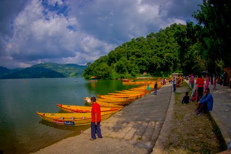 phewa: POKHARA, NEPAL - NOVEMBER 04, 2017: Unidentified people enjoying the view of the lake with wooden boat at Begnas lake in Pokhara, Nepal Editorial