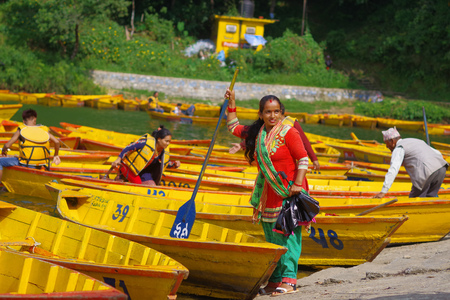 phewa: POKHARA, NEPAL - NOVEMBER 04, 2017: woman holding in her hand a paddle with some yellow boats in the Begnas lake in Pokhara, Nepal