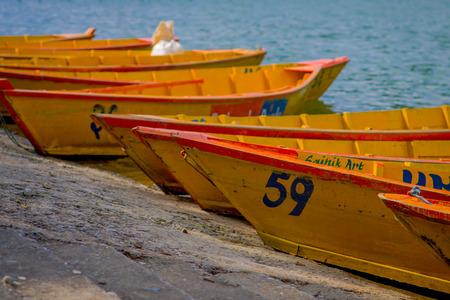 phewa: POKHARA, NEPAL - NOVEMBER 04, 2017: Close up of wooden yellow boats in a row at Begnas lake in Pokhara, Nepal.