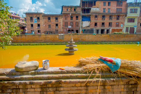 BHAKTAPUR, NEPAL - NOVEMBER 04, 2017: Close up of traditional urban scene with an artificial pond of yellow water at Bhaktapur city, Nepal. Editorial