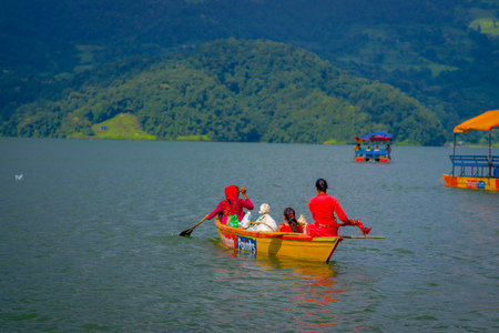 POKHARA, NEPAL - NOVEMBER 04, 2017:Gorgeous family enjoying of a beautiful day over a yellow boat at Begnas lake in Pokhara, Nepal. Editorial